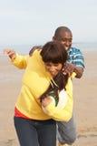 Giovani coppie che giocano rugby sulla festa della spiaggia di autunno Fotografia Stock Libera da Diritti