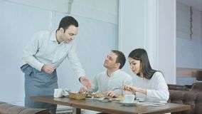 Giovani coppie che godono del loro pranzo al ristorante quando cameriere che porta più alimento fotografia stock