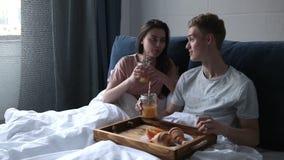 Giovani coppie che godono della prima colazione romantica a letto stock footage