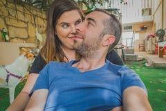 Giovani coppie che godono insieme nel cortile Sono sorridenti, ridenti e facenti i fronti divertenti insieme Fotografia Stock