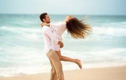 Giovani coppie che godono insieme sulla spiaggia fotografia stock