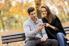 Giovani coppie che guardano felicemente qualcosa sullo smartphone immagine stock libera da diritti