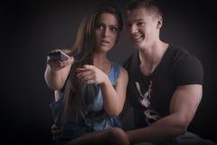 Giovani coppie che guardano TV Immagini Stock