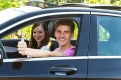 Giovani coppie che guidano in una nuova automobile fotografie stock libere da diritti
