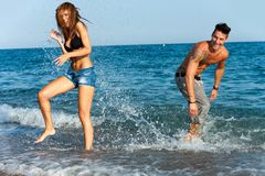 Giovani coppie che hanno divertimento con acqua. Fotografia Stock