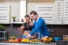 Giovani coppie che hanno divertimento nella cucina Immagine Stock Libera da Diritti