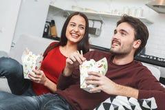 Giovani coppie che hanno romantico uguagliando a casa le tagliatelle di cibo che guardano TV fotografie stock libere da diritti