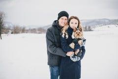 Giovani coppie che hanno una passeggiata con il loro cane in campagna nevosa immagine stock