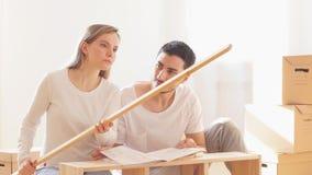Giovani coppie che installano mobilia nella nuova casa con istruzione video d archivio