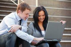 Giovani coppie che lavorano al computer portatile Fotografia Stock Libera da Diritti