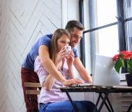 Giovani coppie che lavorano con il computer portatile Fotografie Stock