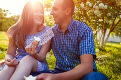 Giovani coppie che mangiano gelato e che chiacchierano fuori Donna ed uomo che raffreddano fuori nel giardino di primavera al tra Fotografia Stock Libera da Diritti