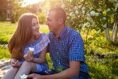 Giovani coppie che mangiano gelato e che chiacchierano fuori Donna ed uomo che raffreddano fuori nel giardino di primavera al tra Immagine Stock Libera da Diritti