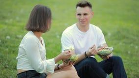 Giovani coppie che mangiano insalata che si siede insieme sull'erba, picnic stock footage