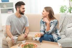 Giovani coppie che mangiano pizza per pranzo in salone fotografie stock libere da diritti