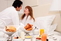 Giovani coppie che mangiano prima colazione in base Immagine Stock