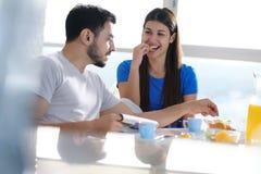 Giovani coppie che mangiano prima colazione a casa la domenica Immagini Stock