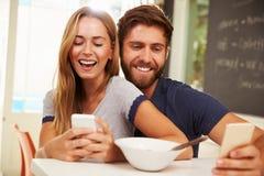 Giovani coppie che mangiano prima colazione mentre per mezzo dei telefoni cellulari Fotografia Stock Libera da Diritti
