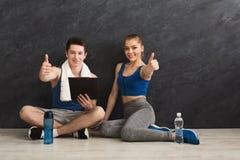 Giovani coppie che mostrano i pollici su che discutono piano di allenamento Fotografia Stock