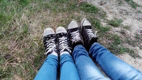 Giovani coppie che mostrano le loro scarpe da tennis sui loro piedi immagini stock libere da diritti