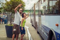Giovani coppie che ondeggiano arrivederci ai loro amici sul bus Immagini Stock