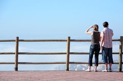 Giovani coppie che osservano fuori al mare dall'alto punto di vista Fotografia Stock