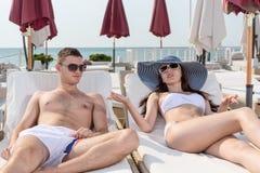Giovani coppie che parlano mentre riposando sulle chaise-lounge fotografia stock libera da diritti