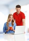 Giovani coppie che passano in rassegna sul computer Fotografia Stock