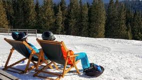 Giovani coppie che prendono il sole ad una stazione sciistica Fotografie Stock