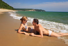 Giovani coppie che prendono il sole alla spiaggia Fotografia Stock