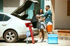 Giovani coppie che preparano per il viaggio di vacanza sull'automobile nel giorno soleggiato fotografia stock libera da diritti