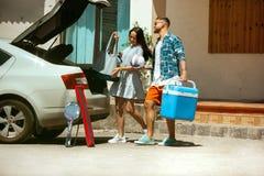 Giovani coppie che preparano per il viaggio di vacanza sull'automobile nel giorno soleggiato immagini stock