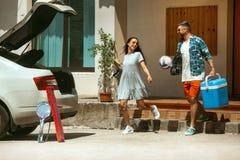 Giovani coppie che preparano per il viaggio di vacanza sull'automobile nel giorno soleggiato immagini stock libere da diritti
