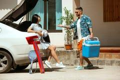 Giovani coppie che preparano per il viaggio di vacanza sull'automobile nel giorno soleggiato fotografia stock