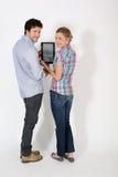 Giovani coppie che presentano nuova compressa isolata Fotografia Stock