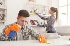 Giovani coppie che puliscono insieme polvere fotografia stock libera da diritti