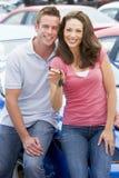 Giovani coppie che raccolgono nuova automobile Fotografie Stock Libere da Diritti