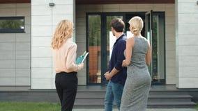 Giovani coppie che restano vicino alla casa di lusso Gruppo di persone che parlano vicino alla nuova casa archivi video
