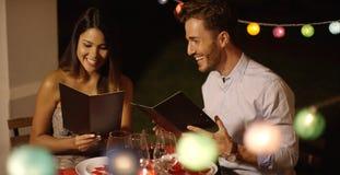 Giovani coppie che ridono come passano attraverso il menu Immagini Stock