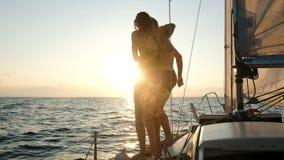 Giovani coppie che saltano dalla navigazione dell'yacht nel mare aperto sul tramonto archivi video