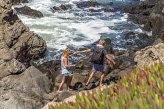 Giovani coppie che scalano le rocce e che godono della vista lungo la linea costiera irregolare di Big Sur Fotografia Stock