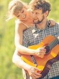 Giovani coppie che si accampano giocando chitarra all'aperto Immagini Stock Libere da Diritti
