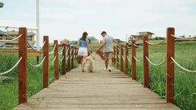 Giovani coppie che si allontanano con il cane del documentalista, ponte di legno, paese, rallentatore archivi video