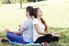 Giovani coppie che si distendono nella posa di yoga fotografia stock