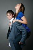 Giovani coppie che si levano in piedi insieme contro una parete grigia Fotografia Stock