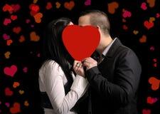 Giovani coppie che si nascondono dietro un heartshape rosso Immagine Stock