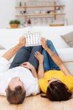 Giovani coppie che si rilassano con un computer del blocco note Fotografia Stock