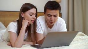 Giovani coppie che si rilassano a letto con il computer portatile Menzogne insieme in camera da letto luminosa stock footage
