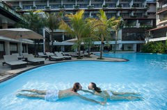 Giovani coppie che si rilassano nello stagno all'hotel Fotografia Stock Libera da Diritti