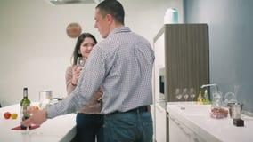 Giovani coppie che si rilassano sulla cucina a casa con vino video d archivio